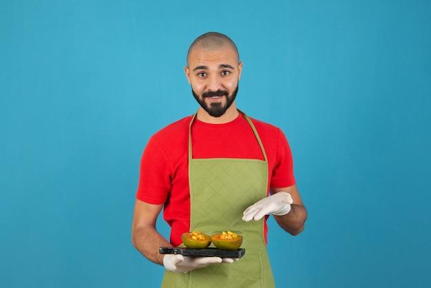Brodaty mężczyzna kucharz w fartuchu i rękawiczkach trzyma ciemną drewnianą deskę z ciastem.