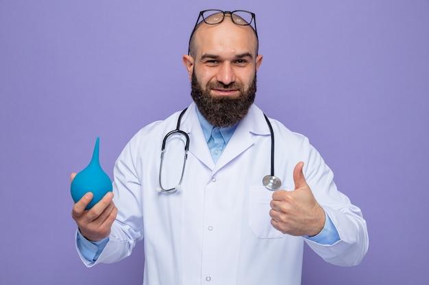 Brodaty mężczyzna lekarz w białym fartuchu ze stetoskopem na szyi, trzymający gruszkę medyczną, patrzący uśmiechnięty pewnie pokazujący kciuki w górę