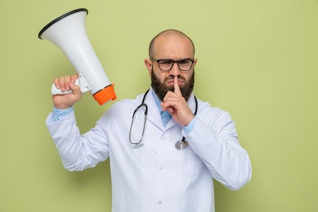 Brodaty mężczyzna lekarz w białym fartuchu ze stetoskopem na szyi w okularach trzymający megafon z poważną twarzą wykonujący gest ciszy z palcem na ustach