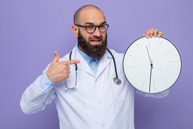 Brodaty mężczyzna lekarz w białym fartuchu ze stetoskopem na szyi w okularach trzymający zegar wskazujący palcem wskazującym uśmiechający się radośnie