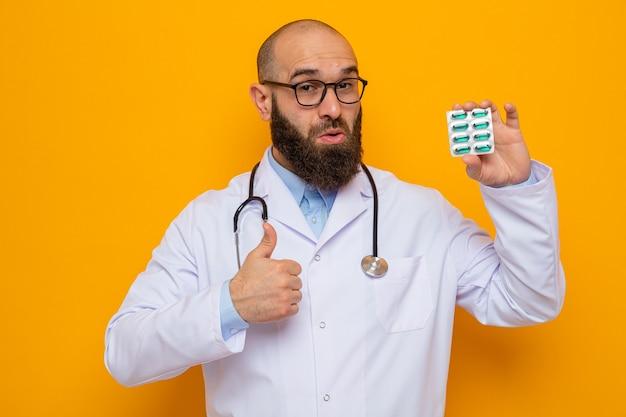 Brodaty mężczyzna lekarz w białym fartuchu ze stetoskopem na szyi w okularach trzymających blister z pigułkami patrzący uśmiechnięty radośnie pokazując kciuk do góry