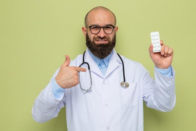 Brodaty mężczyzna lekarz w białym fartuchu ze stetoskopem na szyi w okularach trzymających blister z pigułkami patrzący z uśmiechem na szczęśliwą twarz pokazując kciuk do góry
