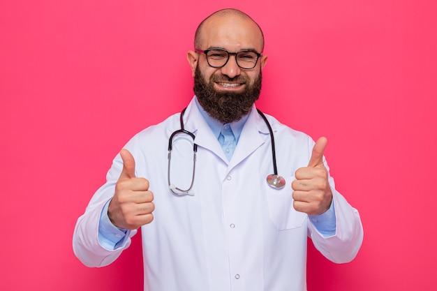 Brodaty mężczyzna lekarz w białym fartuchu ze stetoskopem na szyi w okularach, uśmiechający się radośnie pokazując kciuk do góry