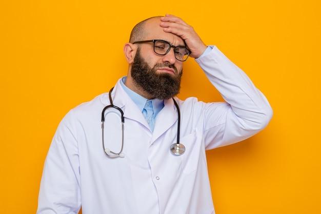 Brodaty mężczyzna lekarz w białym fartuchu ze stetoskopem na szyi w okularach wyglądający na zdezorientowanego i bardzo niespokojnego, trzymający rękę na głowie za błąd stojący na pomarańczowym tle