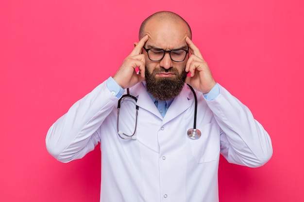 Brodaty mężczyzna lekarz w białym fartuchu ze stetoskopem na szyi w okularach wyglądający na zmęczonego i przepracowanego dotykającego jego skroni cierpiących na ból głowy stojący na różowym tle