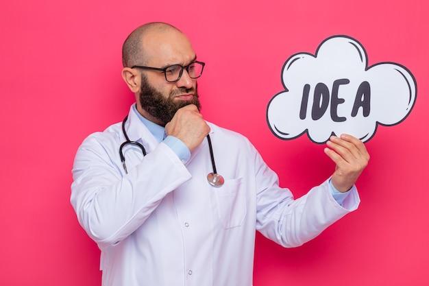 Brodaty mężczyzna lekarz w białym fartuchu ze stetoskopem wokół szyi w okularach trzymający znak dymek z pomysłem na słowo patrząc na to z zamyślonym wyrazem stojącym na różowym tle