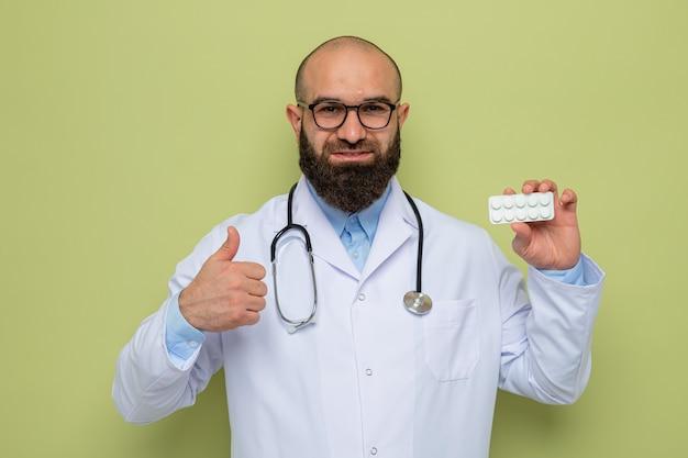 Brodaty mężczyzna lekarz w białym fartuchu ze stetoskopem wokół szyi w okularach trzymających blister z pigułkami, patrząc na kamerę z uśmiechem na szczęśliwej twarzy pokazując kciuk do góry stojący na zielonym tle