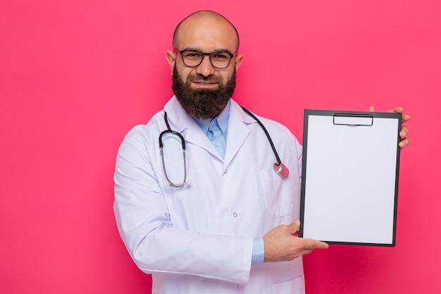 Brodaty mężczyzna lekarz w białym fartuchu ze stetoskopem wokół szyi w okularach trzymających schowek z pustymi stronami patrzący na kamerę uśmiechający się pewnie stojący na różowym tle