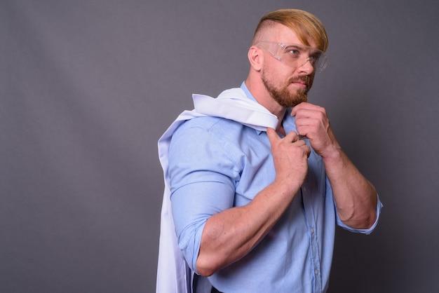 Brodaty mężczyzna lekarz z blond włosami w okularach ochronnych ag