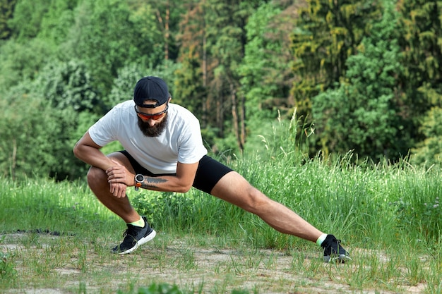 Brodaty mężczyzna lekkoatletycznego robi ćwiczenia w siłowni na świeżym powietrzu w zachodzie słońca.