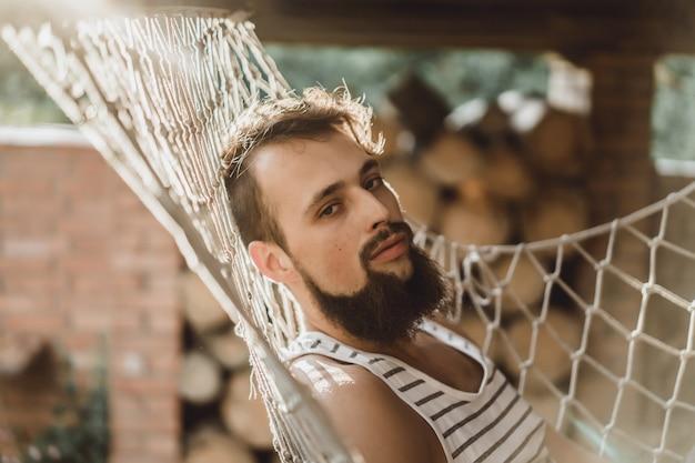 Brodaty mężczyzna leżącego hamaku w ciepły, letni dzień