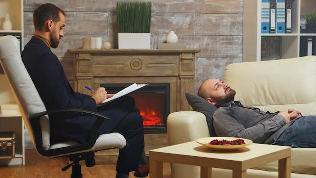 Brodaty mężczyzna leżący na kanapie podczas terapii dla par, opowiadający o konfliktach w związku z żoną.