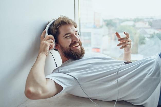Brodaty mężczyzna leżący w pobliżu okna w słuchawkach styl życia. zdjęcie wysokiej jakości