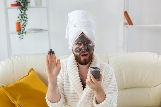 Brodaty mężczyzna ma czystą, świeżą skórę, nosi na twarzy maskę z glinki kosmetycznej i korzysta z zabiegów kosmetycznych w spa w