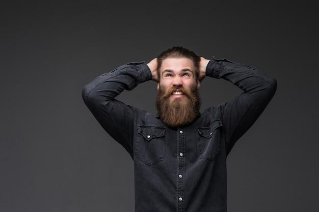 Brodaty mężczyzna młody hipster w furii krzyczy głośno z usta otwarte na szarej przestrzeni.