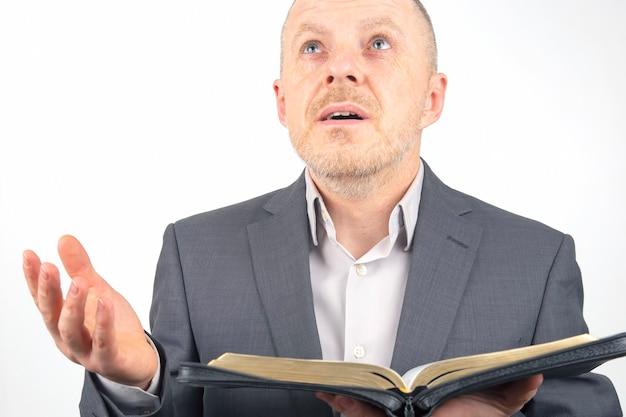 Brodaty mężczyzna modli się, zanim zacznie studiować biblię