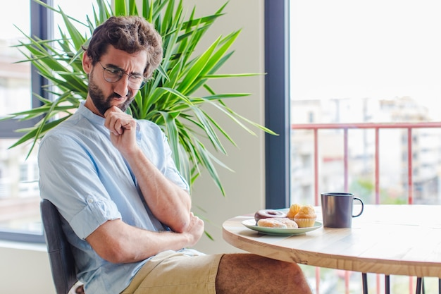Brodaty mężczyzna myślący, wątpiący i zagubiony, z różnymi opcjami, zastanawiający się, jaką decyzję podjąć