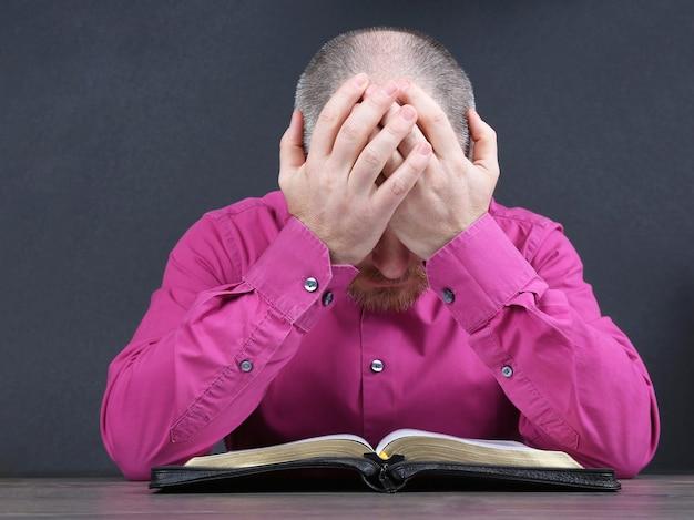 Brodaty mężczyzna myśli o czytaniu książki biblijnej