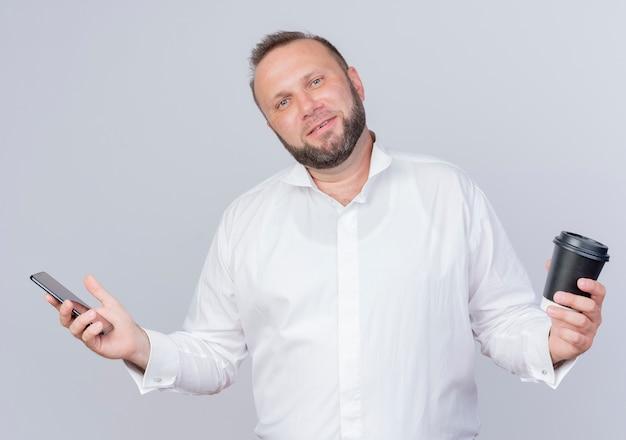 Brodaty mężczyzna na sobie białą koszulę, trzymając smartfon i filiżankę kawy uśmiechnięty, stojąc na białej ścianie