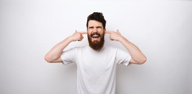 Brodaty mężczyzna nie chce nic słyszeć. obejmuje jego lata i krzyki.