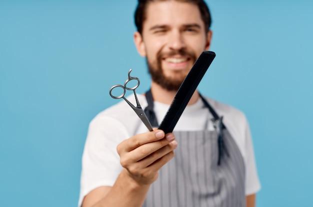 Brodaty mężczyzna nożyczki grzebień niebieskie tło. zdjęcie wysokiej jakości