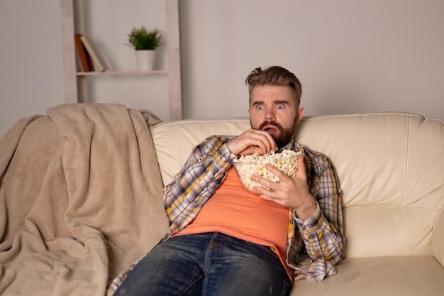 Brodaty mężczyzna ogląda film lub telewizję sportową, jedząc popcorn w domu na mistrzostwach kina nocnego i