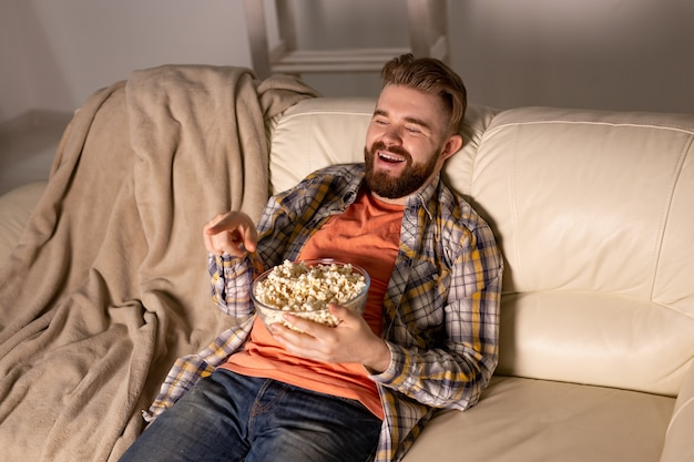 Brodaty mężczyzna ogląda film lub telewizję sportową jedzenie popcornu w domu w nocy. kino, mistrzostwa