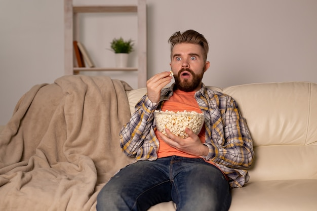 Brodaty mężczyzna ogląda film lub telewizję sportową jedzenie popcornu w domu w nocy. koncepcja kina, mistrzostw i rozrywki.