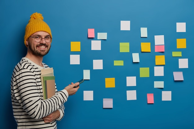 Brodaty mężczyzna organizuje swoje zadania za pomocą karteczek samoprzylepnych