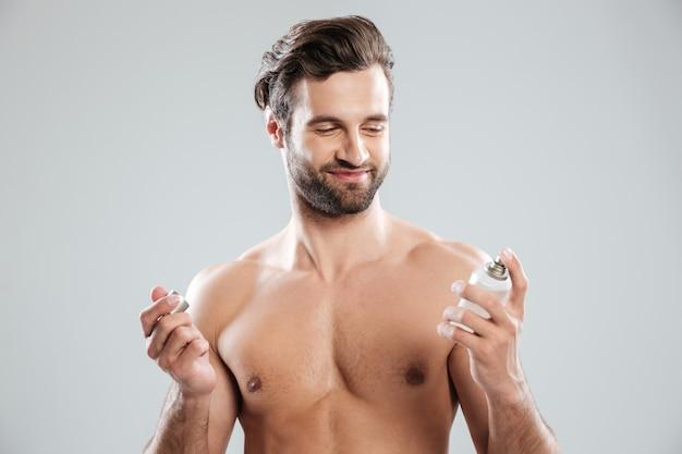 Brodaty mężczyzna otwierając perfum i uśmiechając się