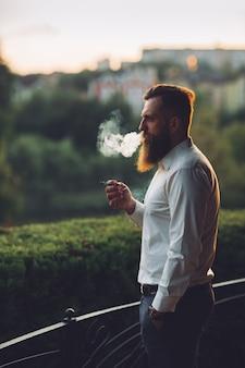 Brodaty mężczyzna pali papierosa przed zachodem słońca.
