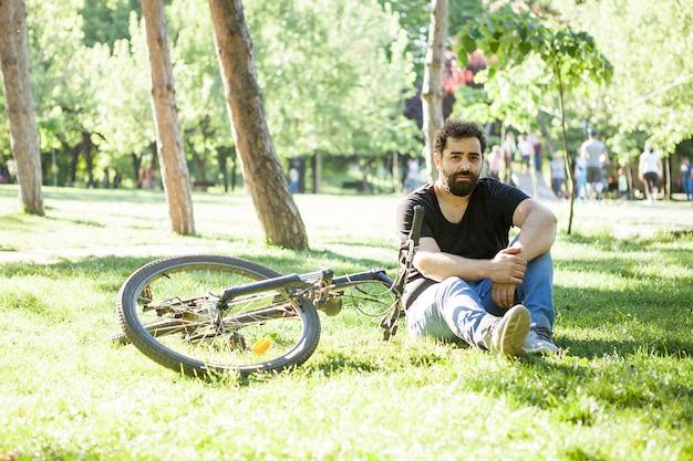 Brodaty mężczyzna patrzący w kamerę obok swojego roweru siedzącego na trawie w parku