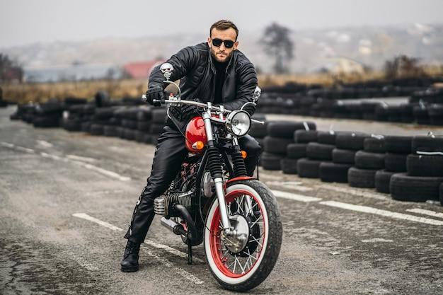 Brodaty mężczyzna patrzeje kamerę w okularach przeciwsłonecznych i skórzanej kurtce podczas gdy siedzący na motocyklu na drodze. za nim jest rząd opon