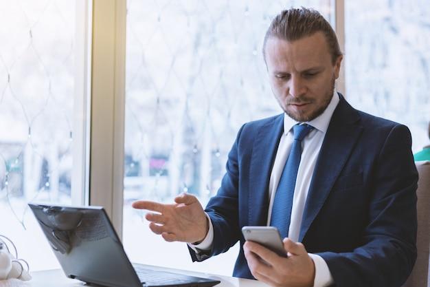 Brodaty mężczyzna patrzeje telefon komórkowego z zdziwionym spojrzeniem salowym w kostiumu