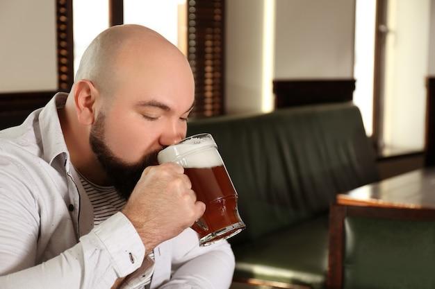 Brodaty mężczyzna pijący piwo w pubie