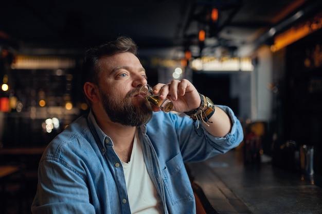 Brodaty mężczyzna pije napój alkoholowy w kasie w barze. jeden mężczyzna odpoczywający w pubie, ludzkie emocje, zajęcia rekreacyjne, życie nocne