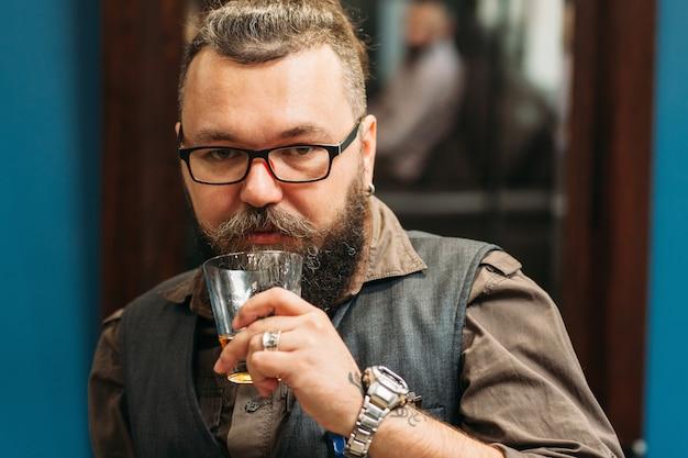 Brodaty mężczyzna pije whisky