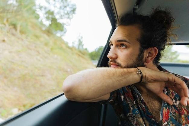 Brodaty mężczyzna podziwiający widoki z okna samochodu