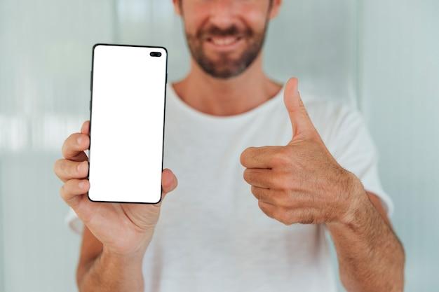 Brodaty mężczyzna pokazuje telefon z kciukiem up