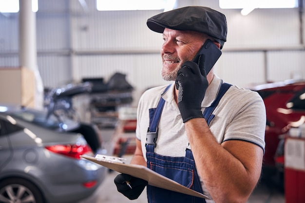 Brodaty mężczyzna pracownik trzyma schowek i uśmiecha się podczas rozmowy przez telefon komórkowy na stacji obsługi naprawy samochodów