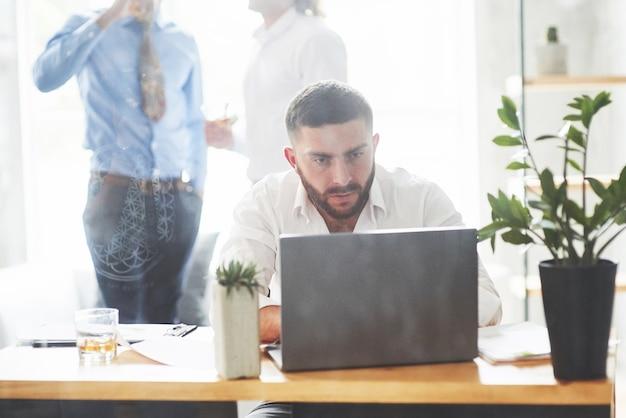 Brodaty mężczyzna pracujący z laptopem w pokoju biurowym z dwoma pracownikami z tyłu