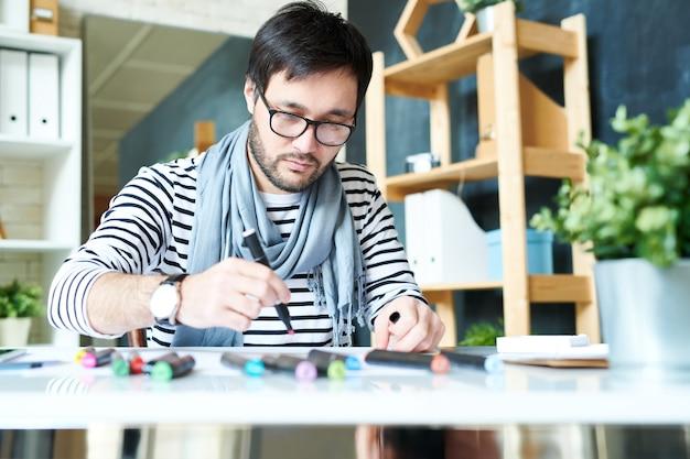 Brodaty mężczyzna pracuje nad nowym obrazem