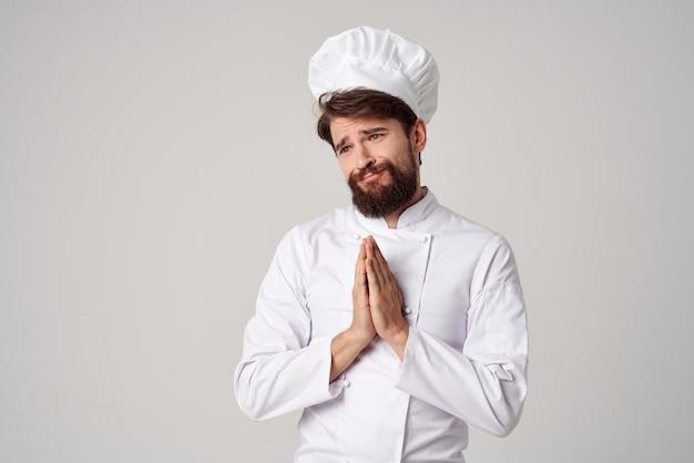 Brodaty mężczyzna pracy jednolitego zawodu kuchnia rzeczy jasne tło