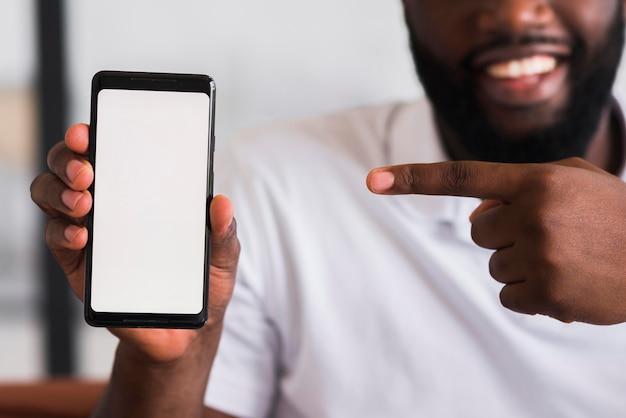 Brodaty mężczyzna prezentuje swój telefon komórkowy