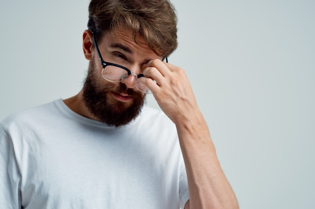 Brodaty mężczyzna problemy ze wzrokiem w białej koszulce zbliżenie