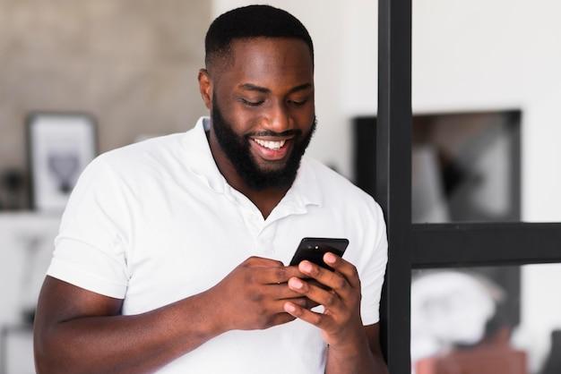Brodaty mężczyzna przegląda telefon komórkowy