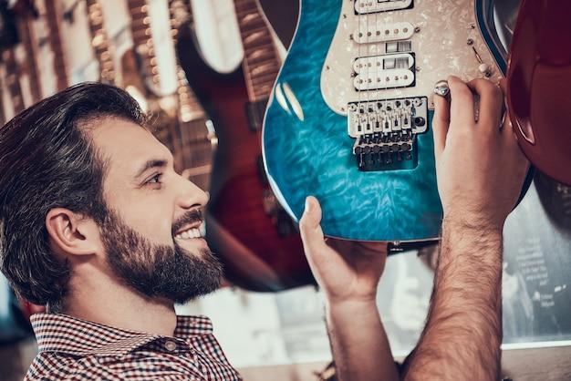 Brodaty mężczyzna przekręca kontrolę głośności na gitarze elektrycznej w sklepie.