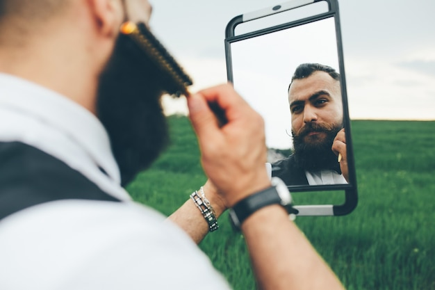 Brodaty mężczyzna przygotowuje się do golenia w polu