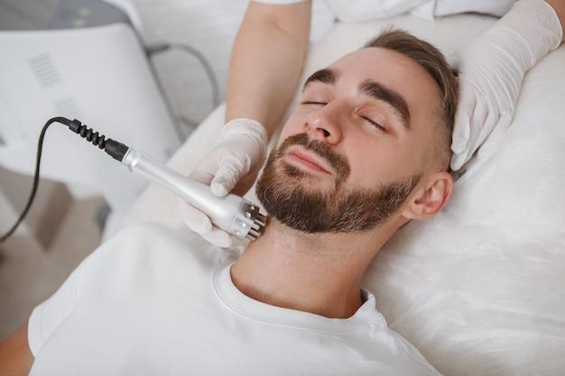 Brodaty mężczyzna relaksujący się w salonie kosmetycznym podczas zabiegu kosmetologii twarzy przez kosmetyczkę