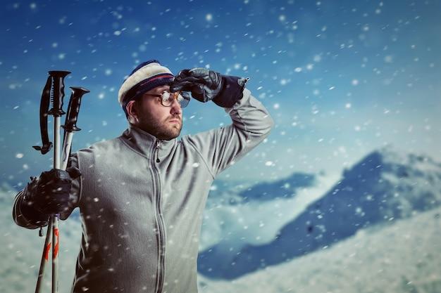 Brodaty mężczyzna retro w okularach w zimowych górach z widokiem